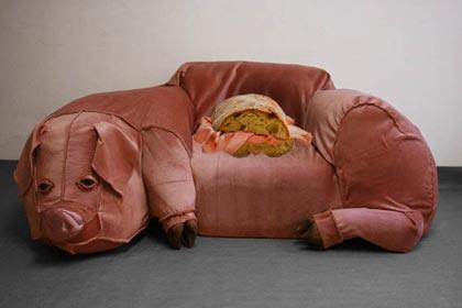 Un divano a forma di porco con un panino alla mortadella sopra.